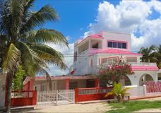 Pink and white Mexican three story house with red fence and palm and flowering trees against a beautiful blue sky with fluffy clou royalty free stock photos