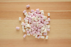 Pink and white mini marshmallows on wood Stock Image