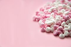 Pink and white mini meringues in the shape of drops, which lie on a pink background. Place for text royalty free stock photography