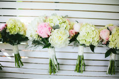 Pink and White Peony Wedding Bouquets. A group of pink and white peony and hydrangea flowers in wedding bouquets for the bridesmaids and bride leaning on a white Royalty Free Stock Photography
