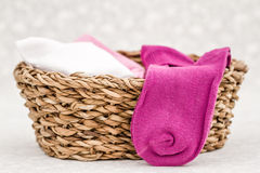 Pink, White and Purple Pair of Child Socks in a Straw Basket Royalty Free Stock Photography