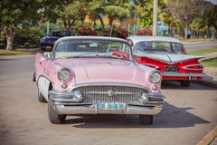 Pink, white red old classic vintage retro cars. Gorgeous old vintage retro car parked in front of tropical garden at Cuban island Varadero, on  beautiful warm Royalty Free Stock Images