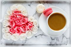 Pink and white roses in heart shaped box and coffee cup on marble table background. Delicious sweets and coffee break. Gift stock image