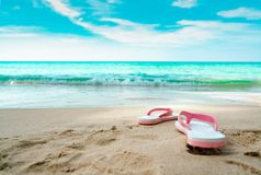 Pink and white sandals on sand beach. Casual style flipflop were removed at seaside. Summer vacation on tropical beach. Fun. Holiday travel on sandy beach royalty free stock photo