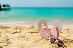 Pink and white sandals, sunglasses on sand beach at seaside. Casual fashion style flipflop and glasses at seashore. Summer. Vacation on tropical beach. Fun royalty free stock photography