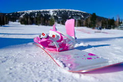 Pink and white snowboard. On a background of mountains Stock Photography