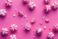 Pink and white striped sweets on pink background. Royalty Free Stock Images