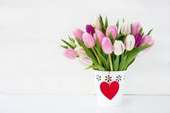 Pink and white tulips bouquet in white vase decorated with red heart. Valentines Day concept. Copy space Stock Photo