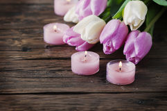 Pink and white tulips and candles on the wooden table Royalty Free Stock Photo