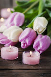 Pink and white tulips and candles on the wooden table Royalty Free Stock Image