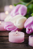 Pink and white tulips and candles on the wooden table. Selective focus Stock Image