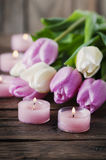 Pink and white tulips and candles on the wooden table. Selective focus Royalty Free Stock Photography
