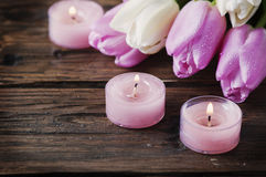 Pink and white tulips and candles on the wooden table. Selective focus Royalty Free Stock Images