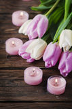 Pink and white tulips and candles on the wooden table Royalty Free Stock Photography