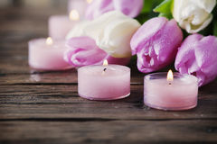 Pink and white tulips and candles on the wooden table. Selective focus Royalty Free Stock Image