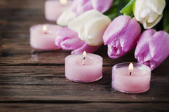 Pink and white tulips and candles on the wooden table. Selective focus Royalty Free Stock Photos