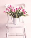 Pink and white tulips on a chair Stock Photos