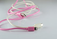 Pink and white USB cable on gray background Stock Photo