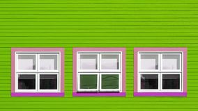 Pink and white windows on lime green wall. Pink and white windows on a lime green wooden wall. Minimalism style of the houses of Iles de la Magdalen, Canada, in royalty free stock photo