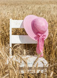 Pink wide brimmed hat with bow hanging on chair Royalty Free Stock Images