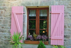 Pink window. Ancient window of a rose-colored stone house with flower plants Stock Photography