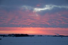 Winter sunset over snow covered field in southern minnesota royalty free stock image