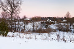 Pink winter sunset under rustic houses Royalty Free Stock Images