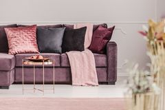 Pink woman`s living room. Copper table next to a violet sofa with decorative cushions in pink woman`s living room interior Royalty Free Stock Image