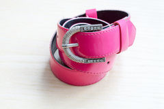 A pink women belts on a light wooden background Stock Photography