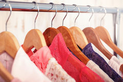 Pink womens clothes on hangers on rack in fashion store. closet. Pink womens clothes on wood hangers on rack in a fashion store. . closet women dresses, blouses Royalty Free Stock Images