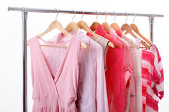 Pink womens clothes on hangers on rack on white background. clos. Pink womens clothes on wood hangers on rack on white background. closet women dresses, blouses royalty free stock photography