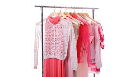 Pink womens clothes on hangers on rack on white background. clos. Pink womens clothes on wood hangers on rack on white background. closet women dresses, blouses royalty free stock photos