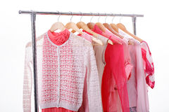 Pink womens clothes on hangers on rack on white background. clos. Pink womens clothes on wood hangers on rack on white background. closet women dresses, blouses royalty free stock image