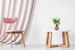 Pink drapes in elegant interior. Pink wooden chair against drapes next to table with flowers in vase in elegant white interior royalty free stock images