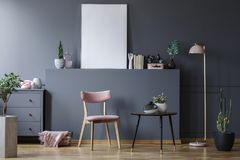 Pink wooden chair at black table in grey living room interior with mockup of empty poster