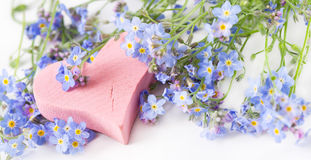 Pink wooden heart among wildflowers for greeting card. Royalty Free Stock Images