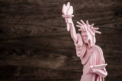 Pink Wooden Model of Statue of Liberty on Brown Wooden Backgroun Royalty Free Stock Images