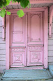 Pink wooden retro cracked door at the entrance of old building. Pink wooden stylish retro cracked door with chipping paint at the entrance of old building on the Stock Images