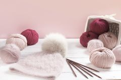 Pink wool yarn in coils with warm hat Stock Photos