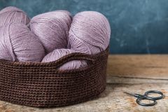 Pink wool yarn with scissors in the crocheted basket. Knitting pink wool yarn in the crocheted basket Stock Images