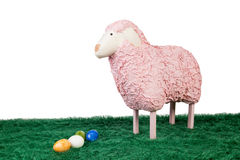 Pink woolly sheep with Easter eggs. Pretty cuddly pink woolly toy sheep standing on green grass with a group of colourful handpainted marbled Easter eggs with stock photos