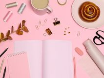 Pink work table with notes paper, office accessories, coffee, baking stock photography
