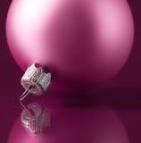 Pink xmas ball on dark purple background Stock Image