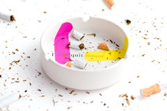 Pink and yellow band-aid sticked on white ashtray with destroyed cigarrette around Stock Image