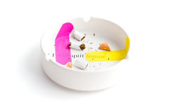 Pink and yellow band-aid sticked on white ashtray to emphasize words `i quit` Stock Photo