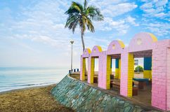 Pink & Yellow Beach Resting Place. Beach Resting Place with pink and yellow bricks with calm sea and a lone coconut tree in the background. From Muscat, Oman royalty free stock photos