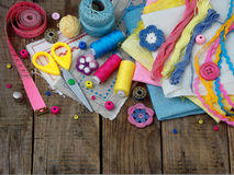 Pink, yellow and blue accessories for needlework on wooden background. Knitting, embroidery, sewing. Small business. Income from h Royalty Free Stock Images