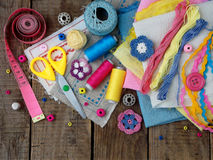 Pink, yellow and blue accessories for needlework on wooden background. Knitting, embroidery, sewing. Small business. Income from h Stock Photos