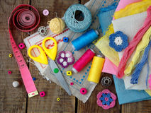 Pink, yellow and blue accessories for needlework on wooden background. Knitting, embroidery, sewing. Small business. Income from h. Pink, yellow and blue Royalty Free Stock Photo