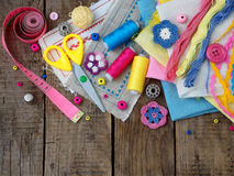 Pink, yellow and blue accessories for needlework on wooden background. Knitting, embroidery, sewing. Small business. Income from h Stock Photo